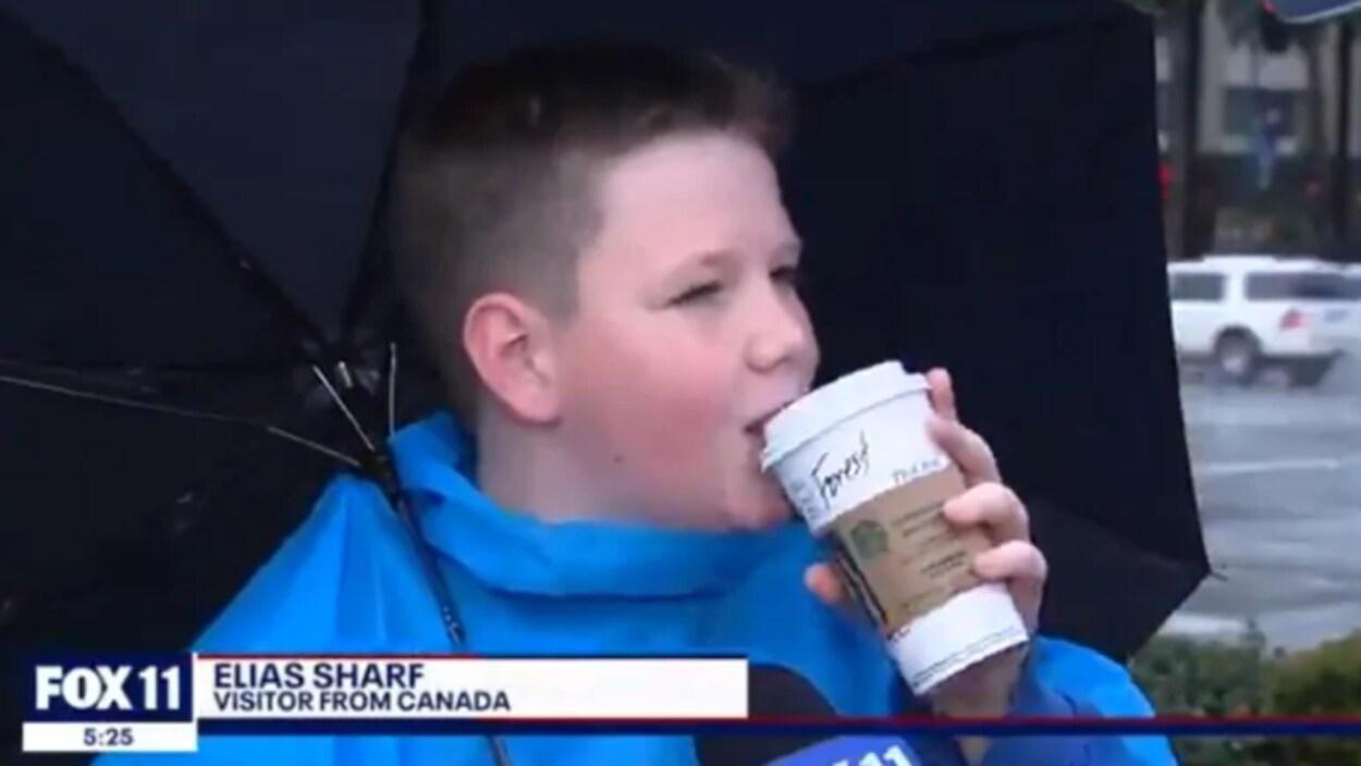 Elias Scharf boit une gorgée de chocolat chaud avec un parapluie sur son épaule.