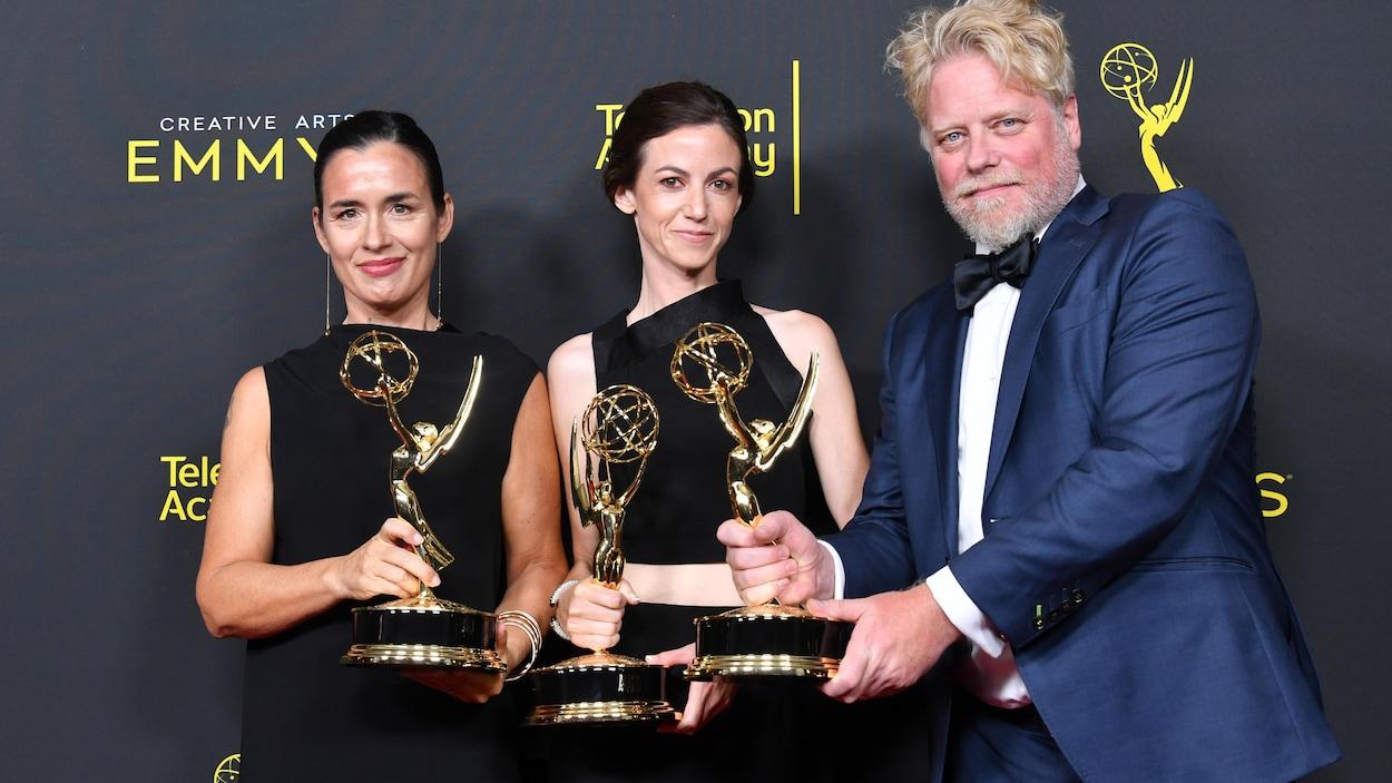 Les trois personnes sourient et ont chacune une statuette en main.