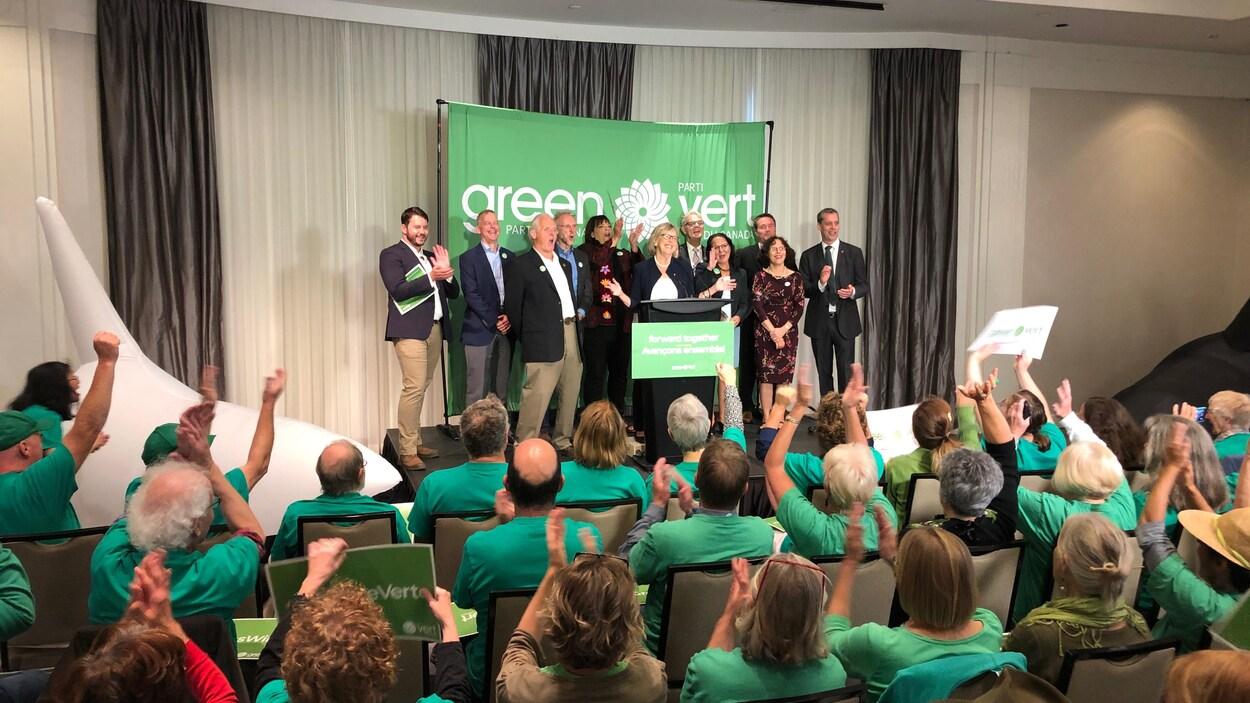 Les candidats sont debout sur la scène, applaudis par les militants.