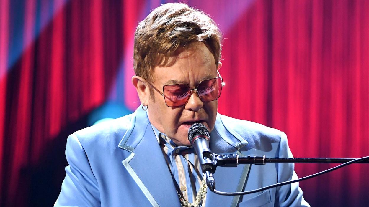 L'homme est assis au piano et porte des lunettes roses.