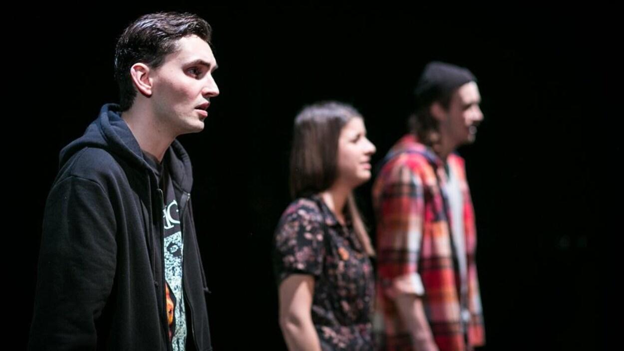 Un jeune homme en avant-plan et deux autres comédiens, une femme et un homme, sont sur scène.