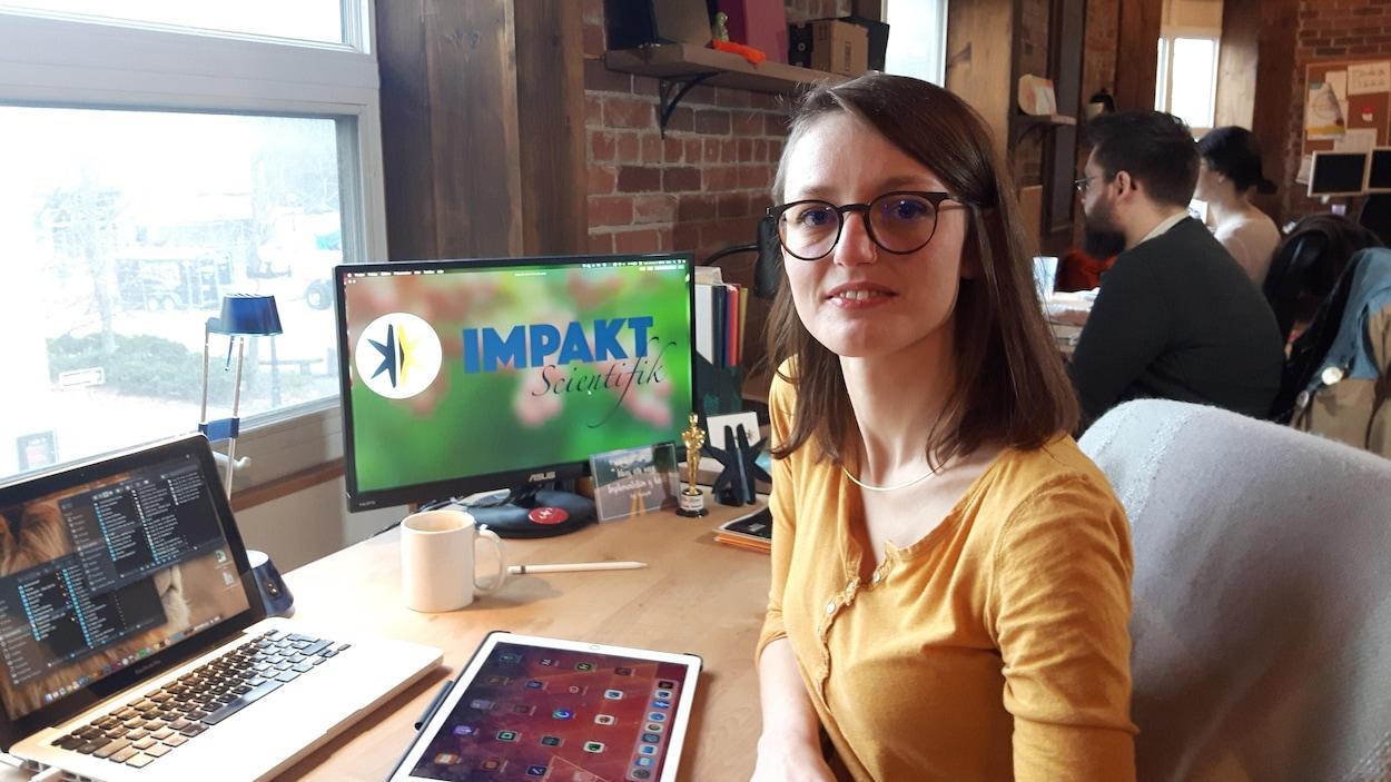 Émilie Dubois sur son lieu de travail, devant un ordinateur et une tablette.