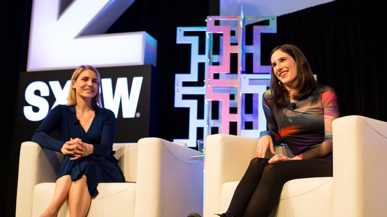 Deux femmes sont assises dans des fauteuils sur une scène pour une conférence.