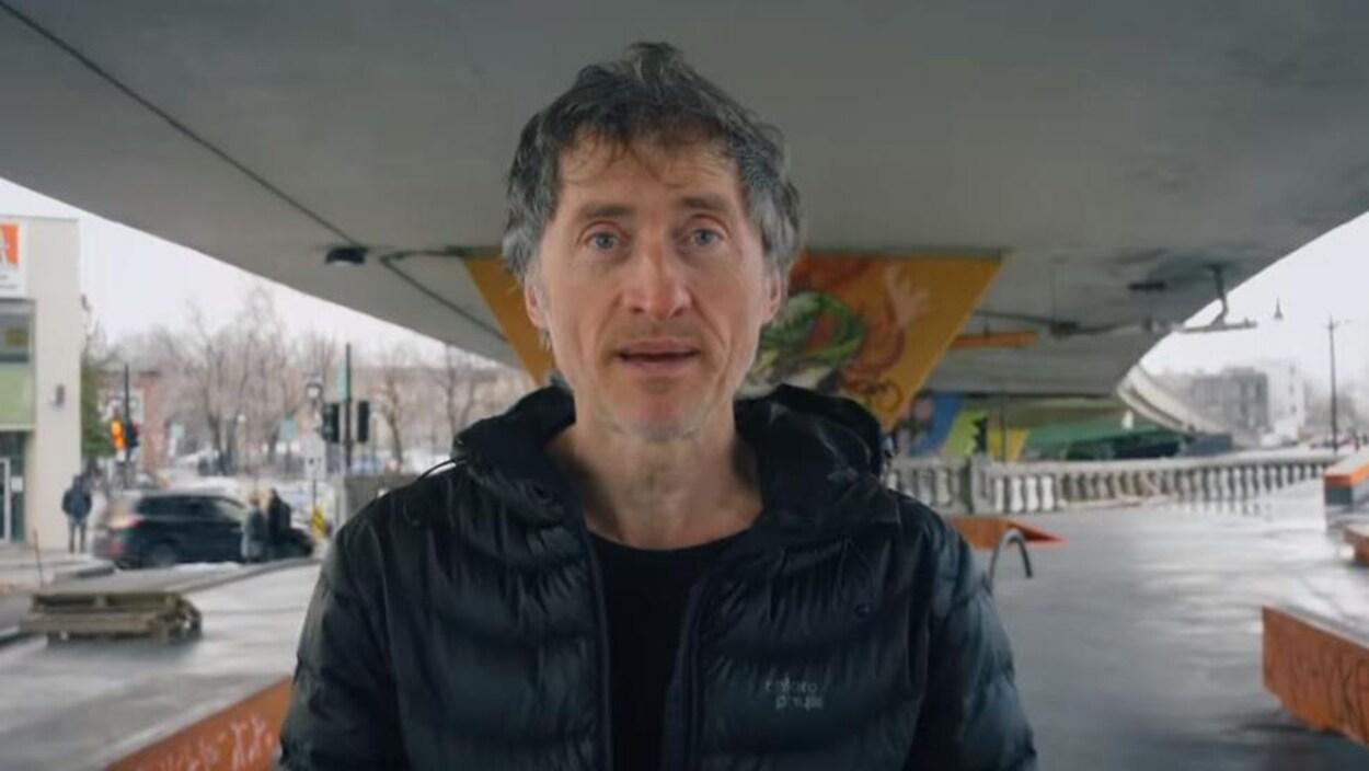 L'homme parle à la caméra sous un viaduc.