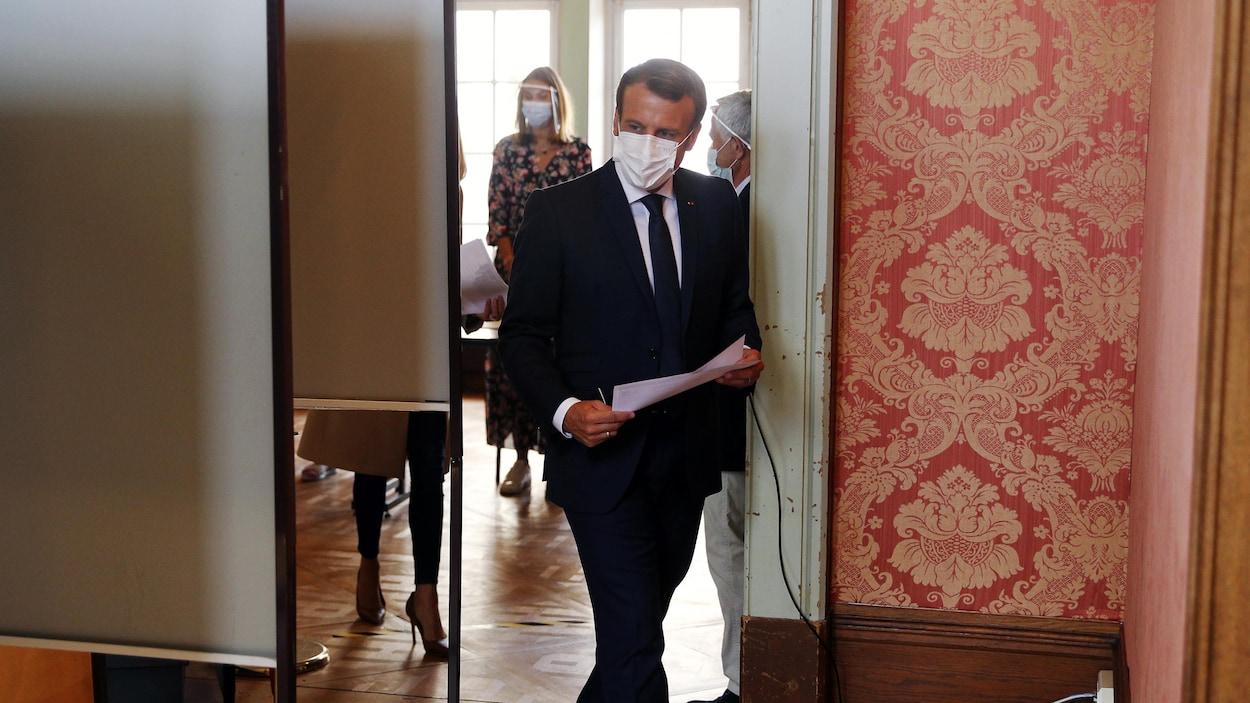 M. Macron, masqué, s'avance vers l'isoloir, un papier et un crayon à la main.