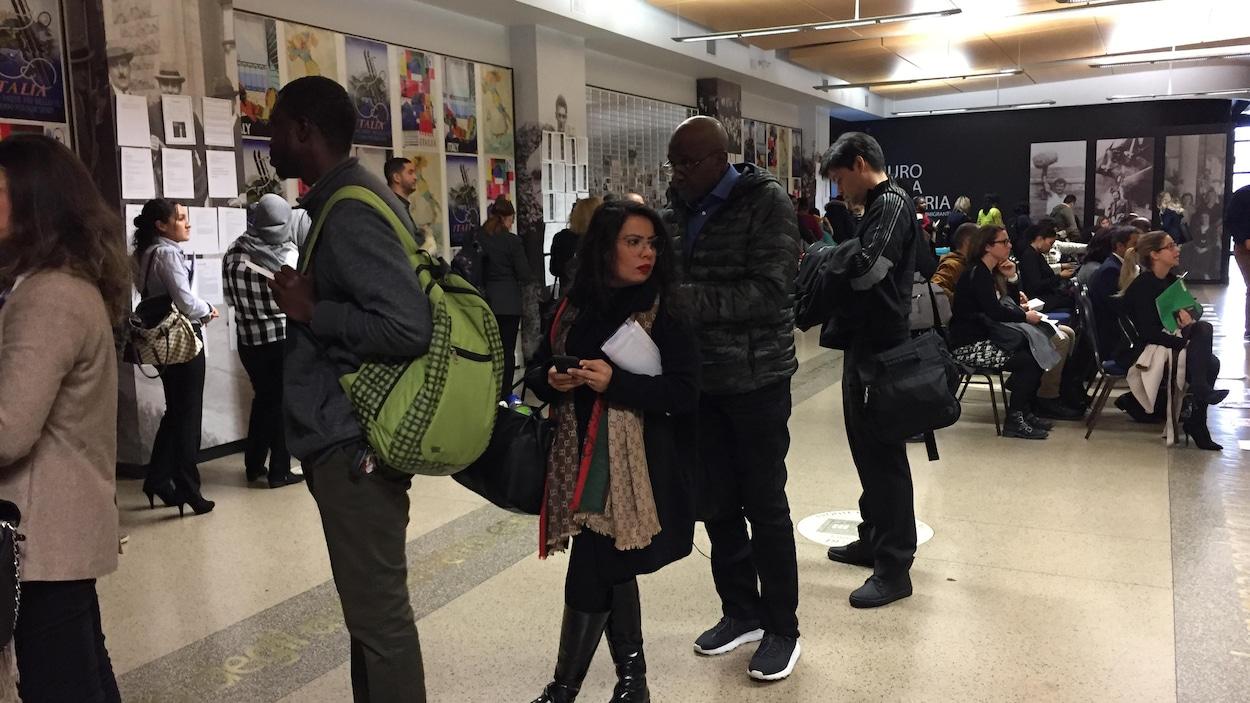 """On voit des immigrants patienter debout dans une salle avant d'obtenir une entrevue pour un emploi lors de la cinquième édition de l'événement """"Speed Jobbing à Montréal organisé par La Maisonnée."""