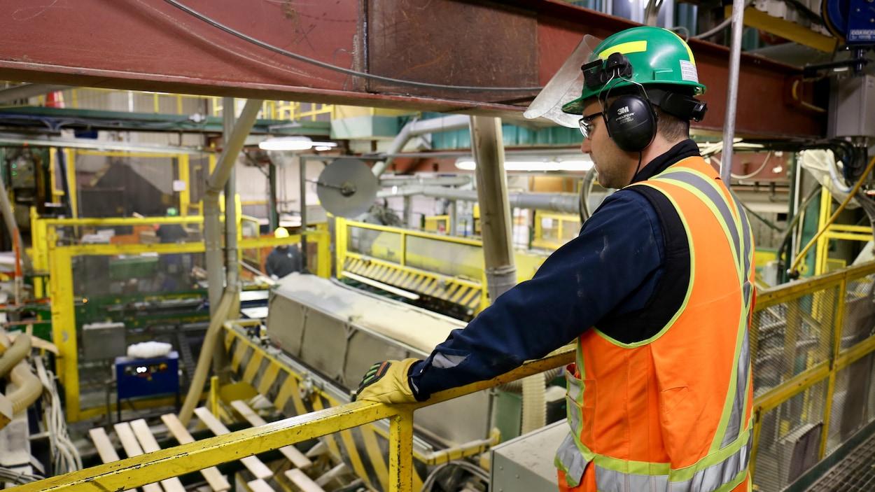 Un employé de Produits Forestiers Résolu observe la machinerie.