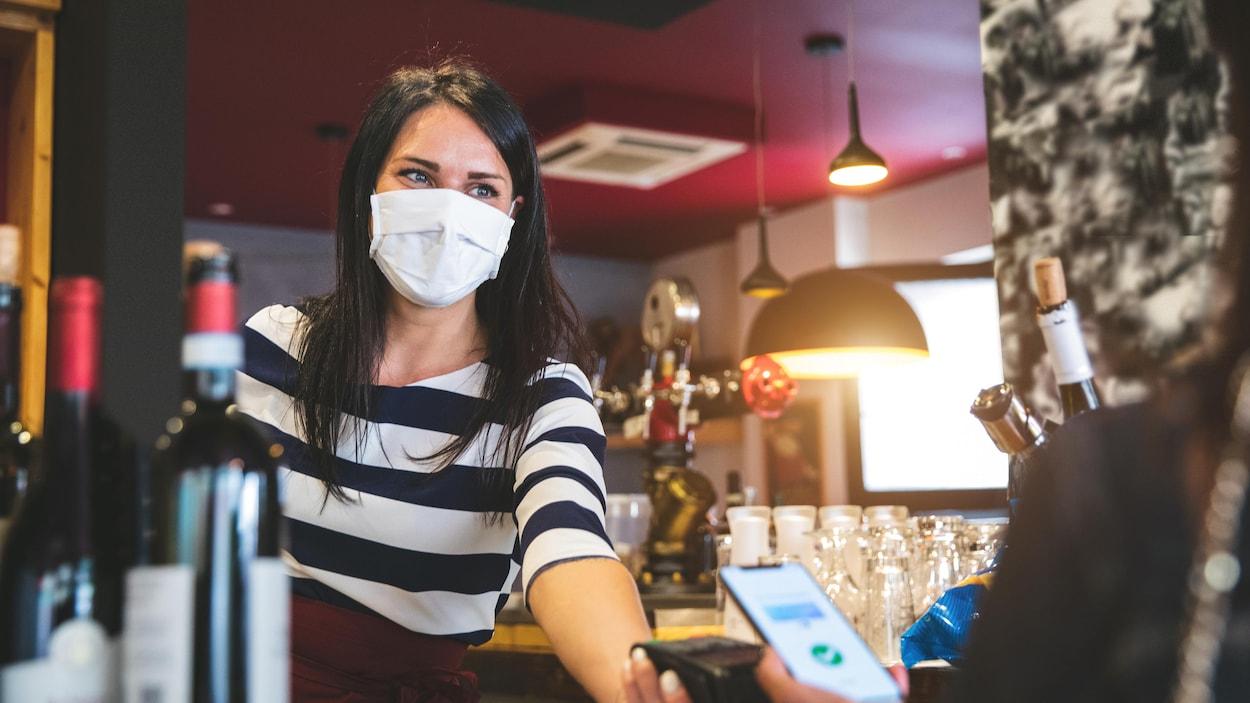 Une employée d'un restaurant, le visage couvert d'un masque, tend la machine interac à une cliente qui va payer avec son téléphone cellulaire.