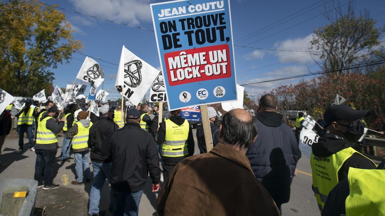 Des syndiqués portent une pancarte sur laquelle il est écrit « Jean Coutu : on trouve de tout, même un lock-out ».