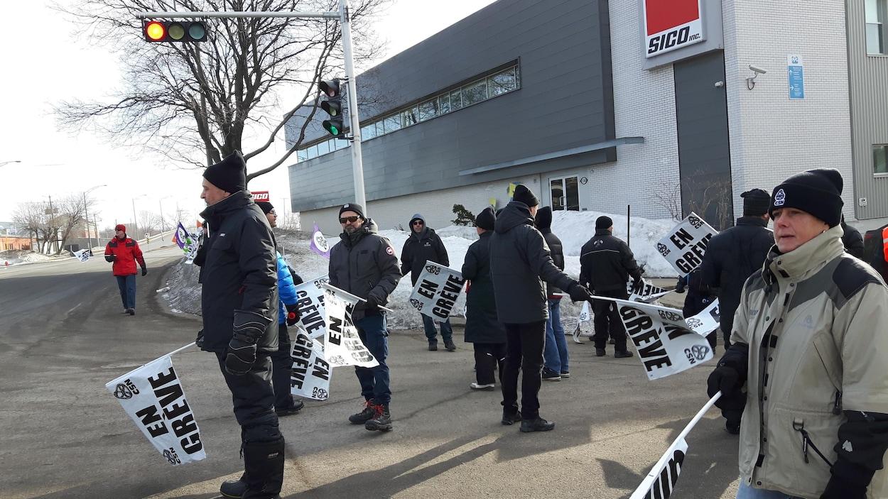 Des travailleurs munis de pancartes manifestent devant l'usine Sico