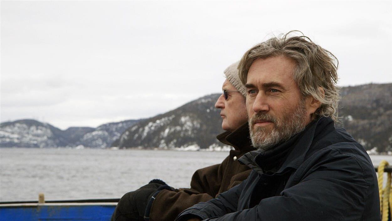 Deux hommes sur une embarcation regardent au loin.