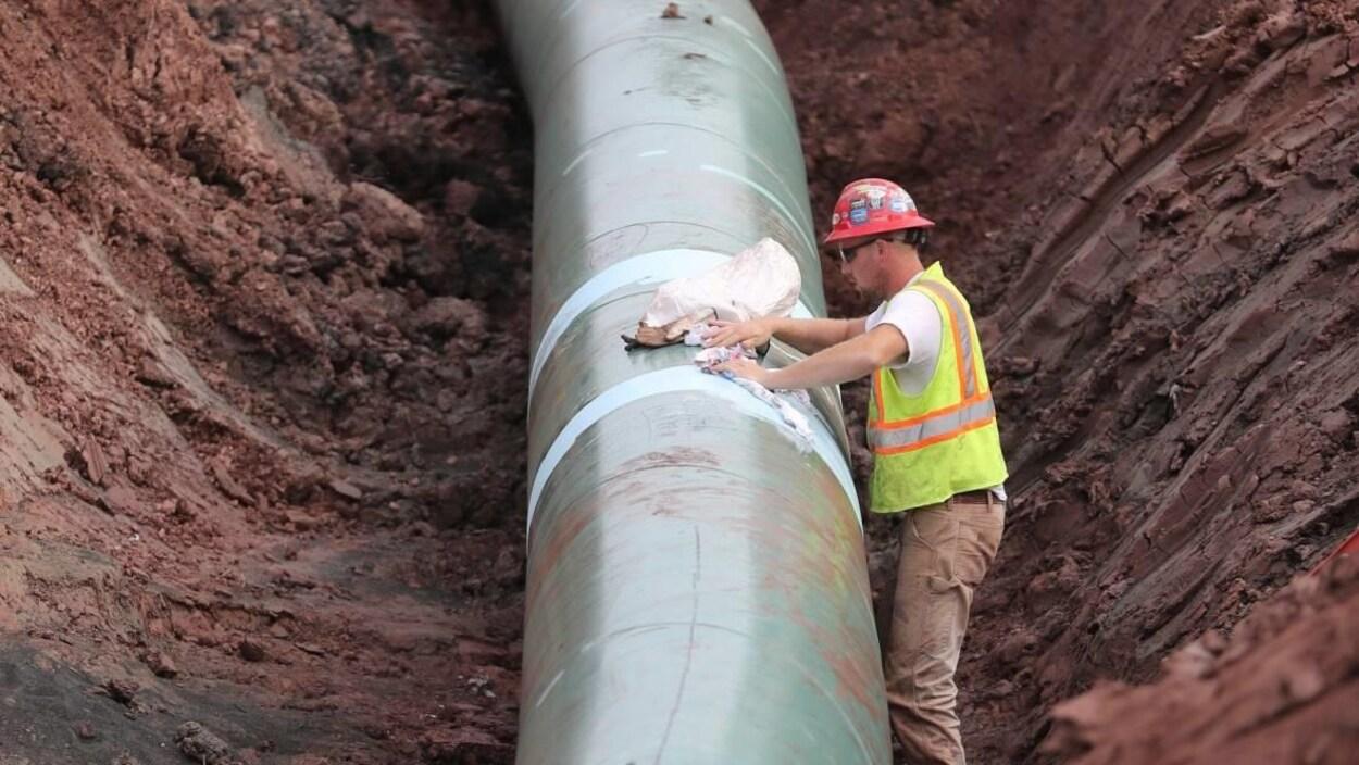 Un travailleur pose les dernières touches au pipeline, posé au fond d'un fossé de terre.