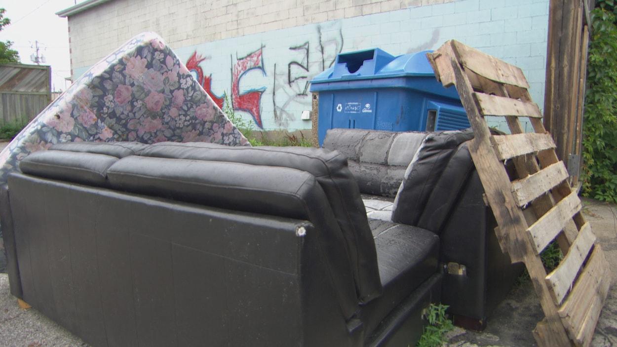 Un matelas, un vieux canapé et une structure de bois près d'un bac de recyclage bleu