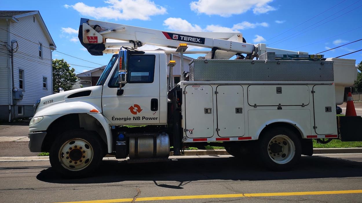 Un camion de la société Énergie Nouveau-Brunswick le long d'une rue.