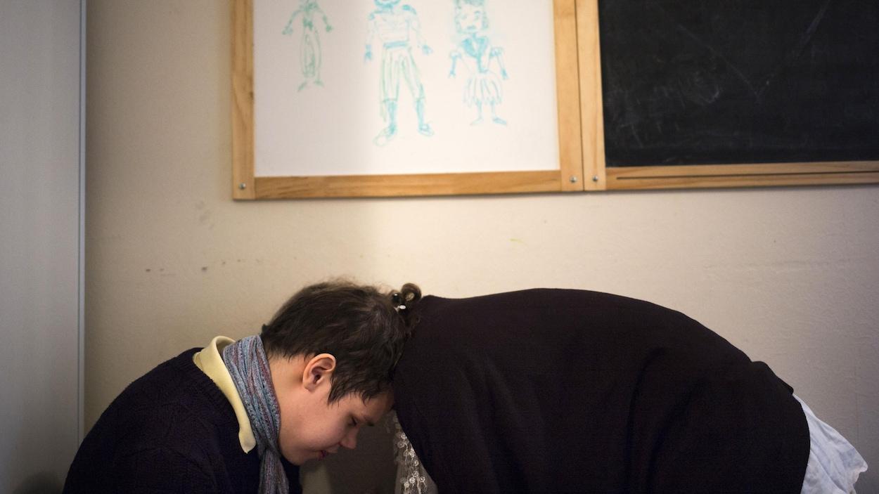 Un jeune garçon autiste se confie à une intervenante, sous un tableau rempli de dessins montrant des héros et des princesses.