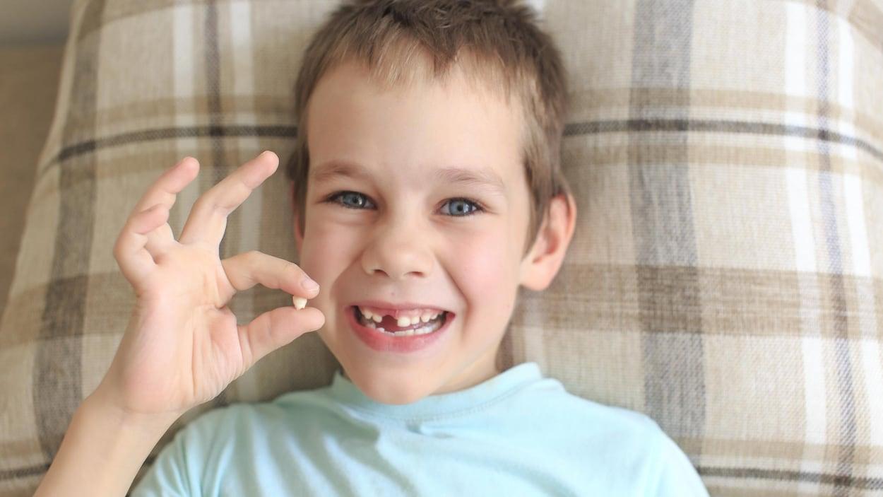 Un garçon se réjouit d'avoir perdu l'une de ses dents de bébé.