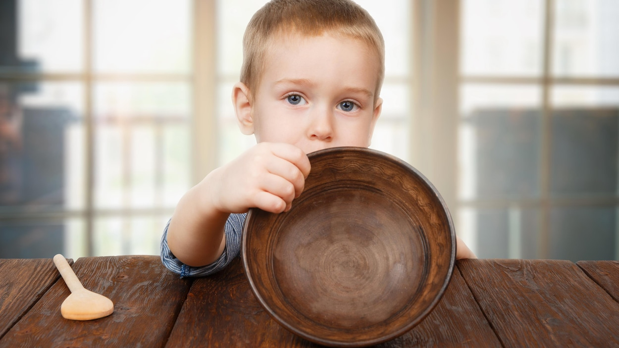 Un petit garçon, l'air sérieux, semble nous montrer un bol vide. Il est assis à une table en bois et une cuillère de bois est posée près de lui.