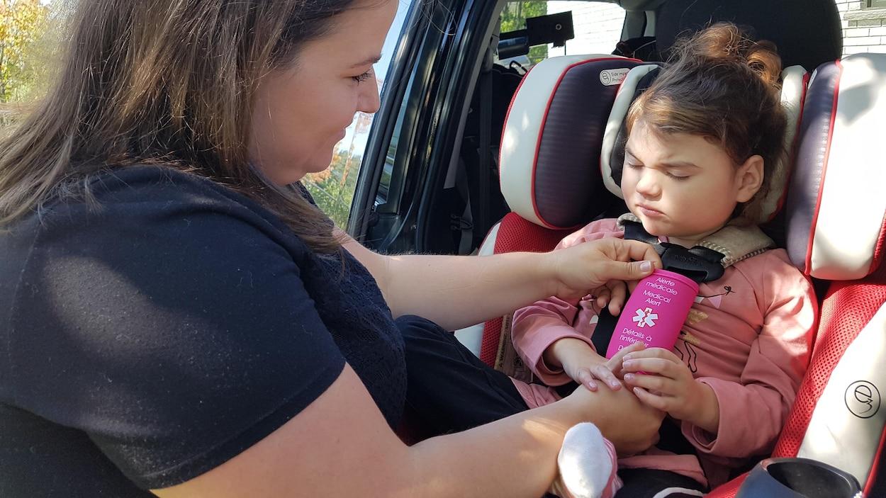 Une mère attache sa fille dans un véhicule