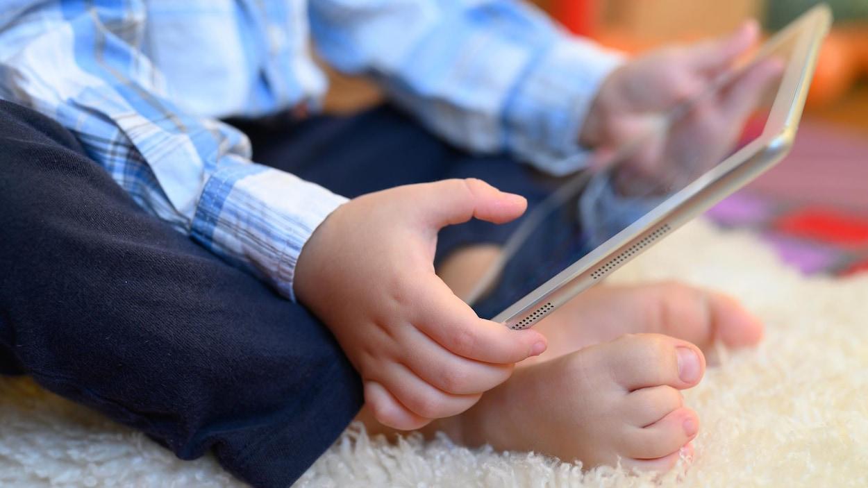 Un enfant tient une tablette dans ses mains