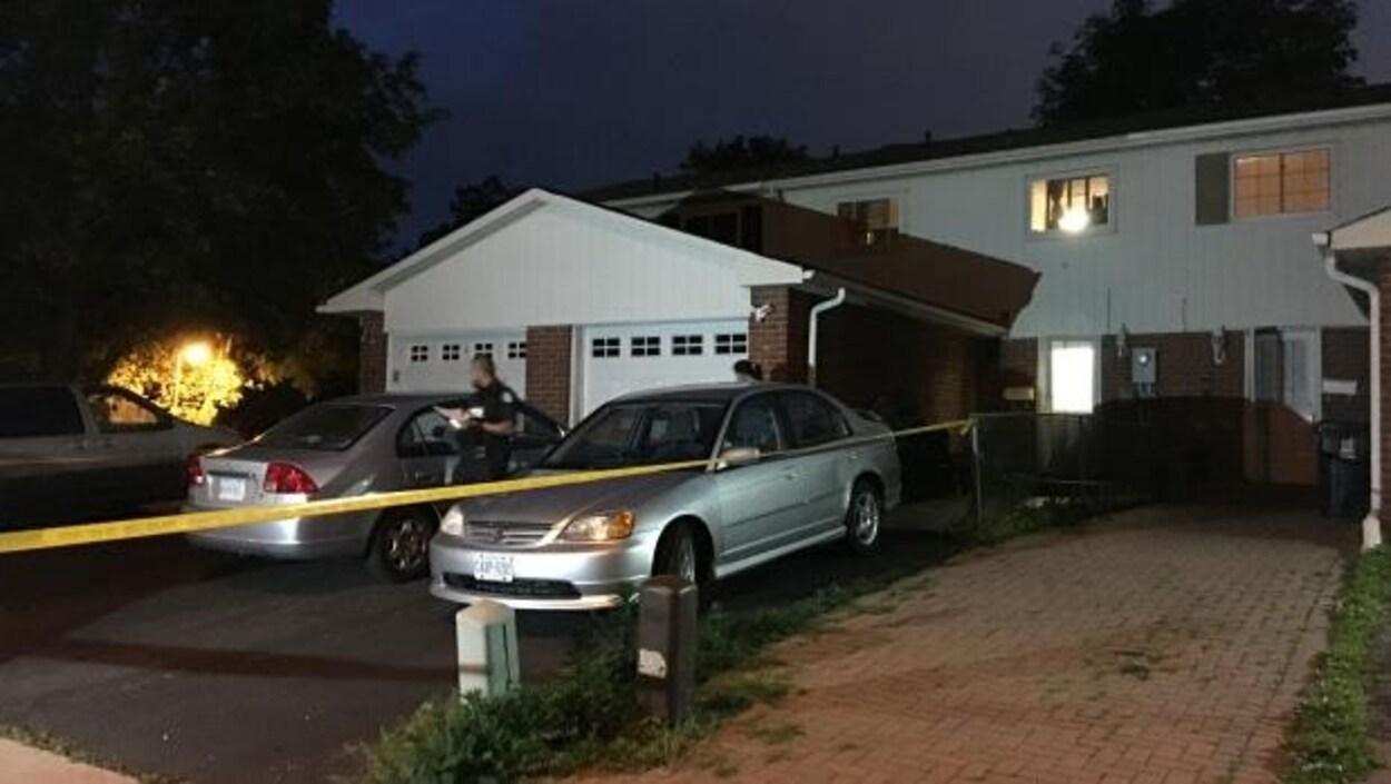Une maison jumelée avec des voitures et un policier à l'avant.