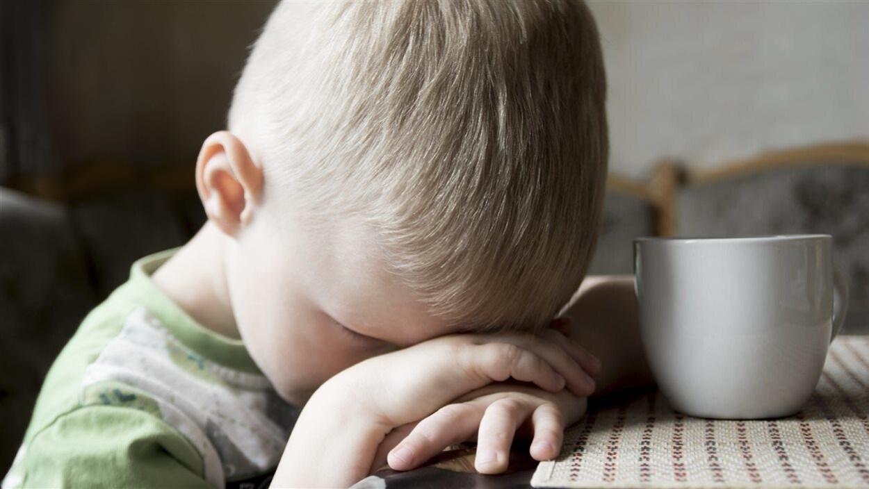 Un enfant triste se cache le visage avec ses mains. Il est assis à table devant une tasse