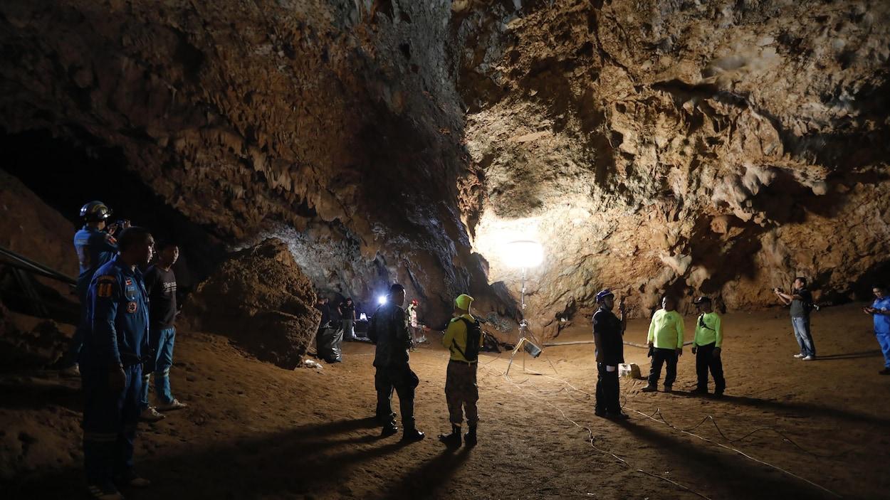 Une dizaine de personnes qui forment l'équipe de sauvetage se trouvent dans une grotte. Certains portent des lampes de poche.