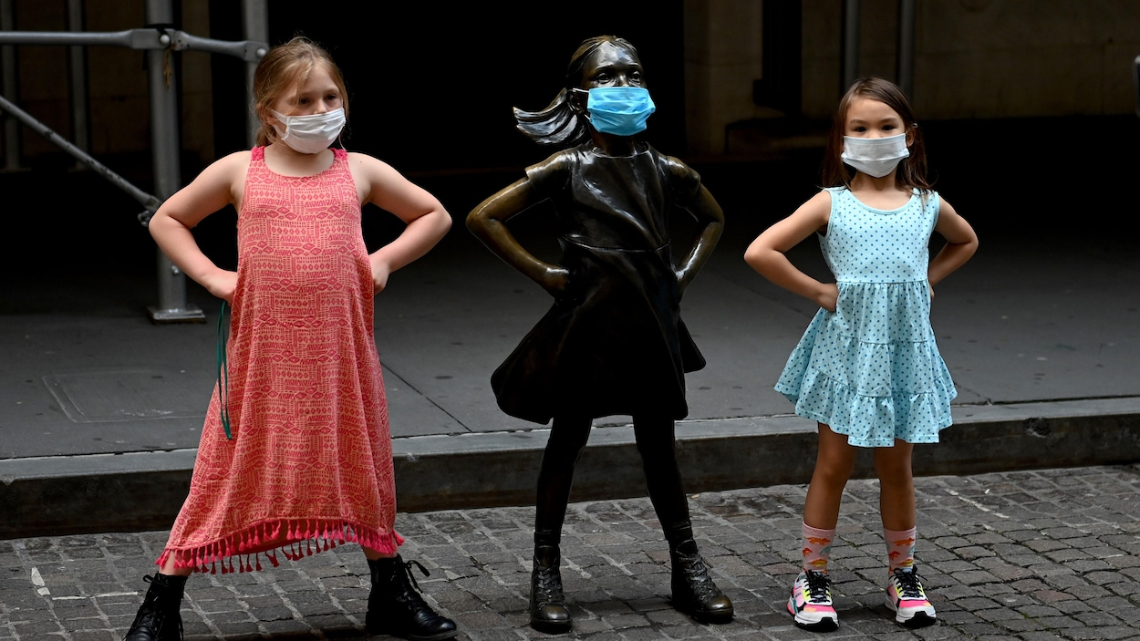 Deux fillettes portant des masques posent à côté de « La fillette sans peur » de Kristen Visbal, à New York.