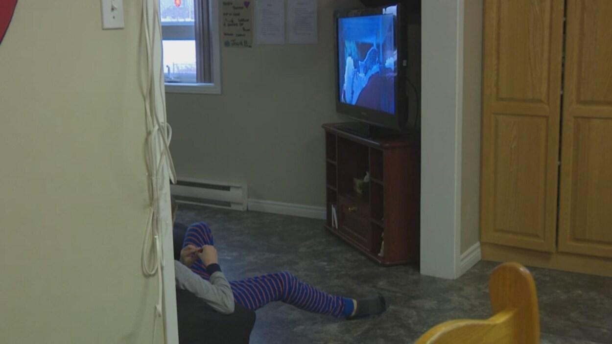Un enfant assis contre un mur regarde la télévision.