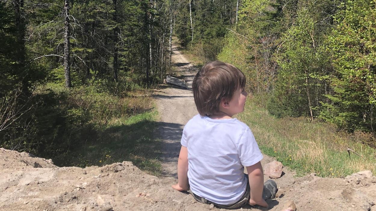 Un enfant devant un terrain boisé au parc de la Colline