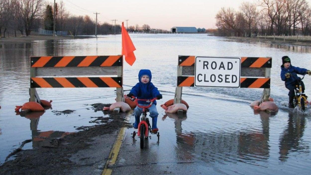 Des enfants à vélo dans une rue inondée.