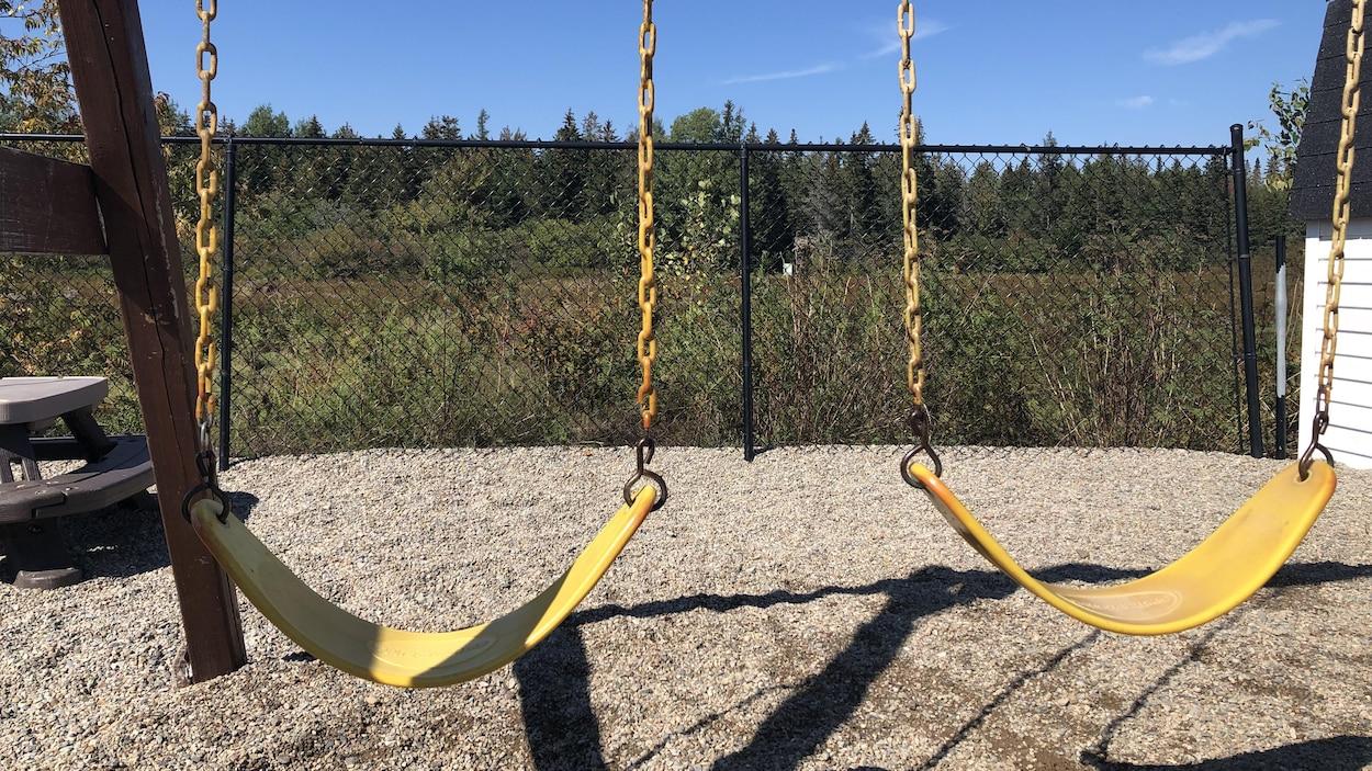 Deux balançoires jaunes sur un terrain de jeu.