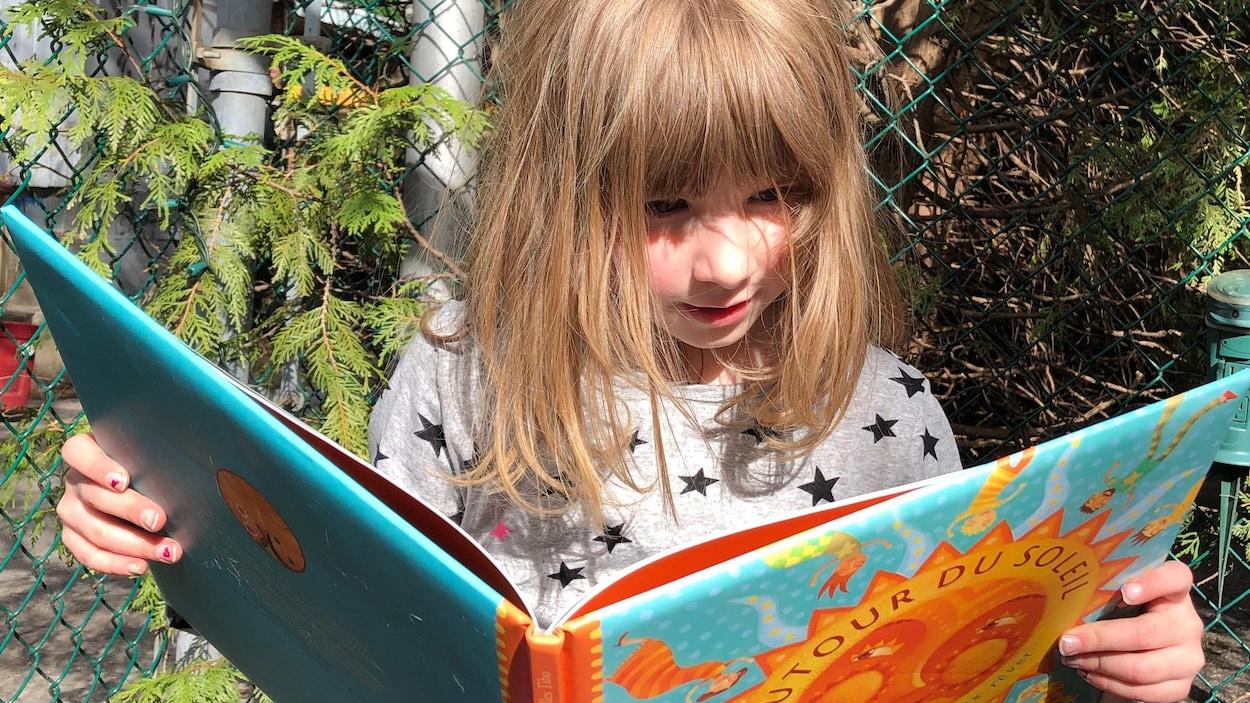 La fillette regarde un livre ouvert.