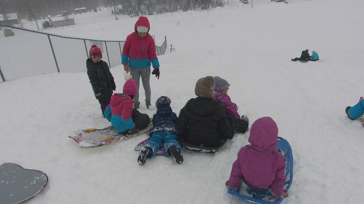 Des enfants, accompagnés d'adultes, descendent une pente de neige sur des planches.