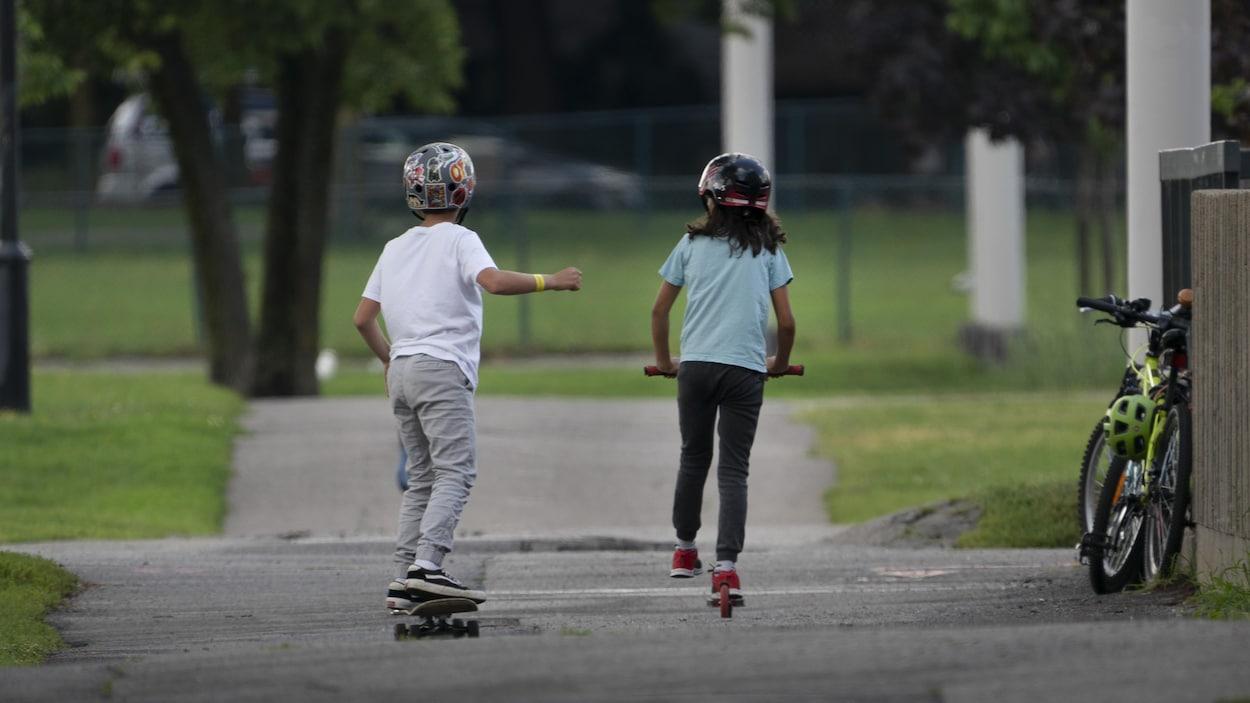 Un jeune garçon se déplace en planche à roulettes, tandis qu'une fillette est en trottinette.