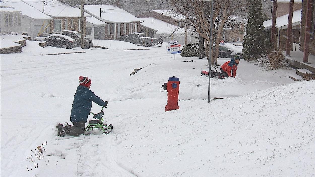 Des enfants profitent de la première chute de neige importante à Baie-Comeau.