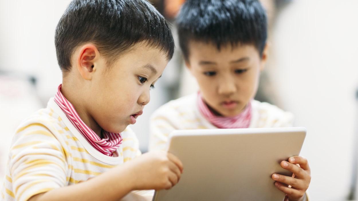 Deux petits garçons regardent une tablette électronique.