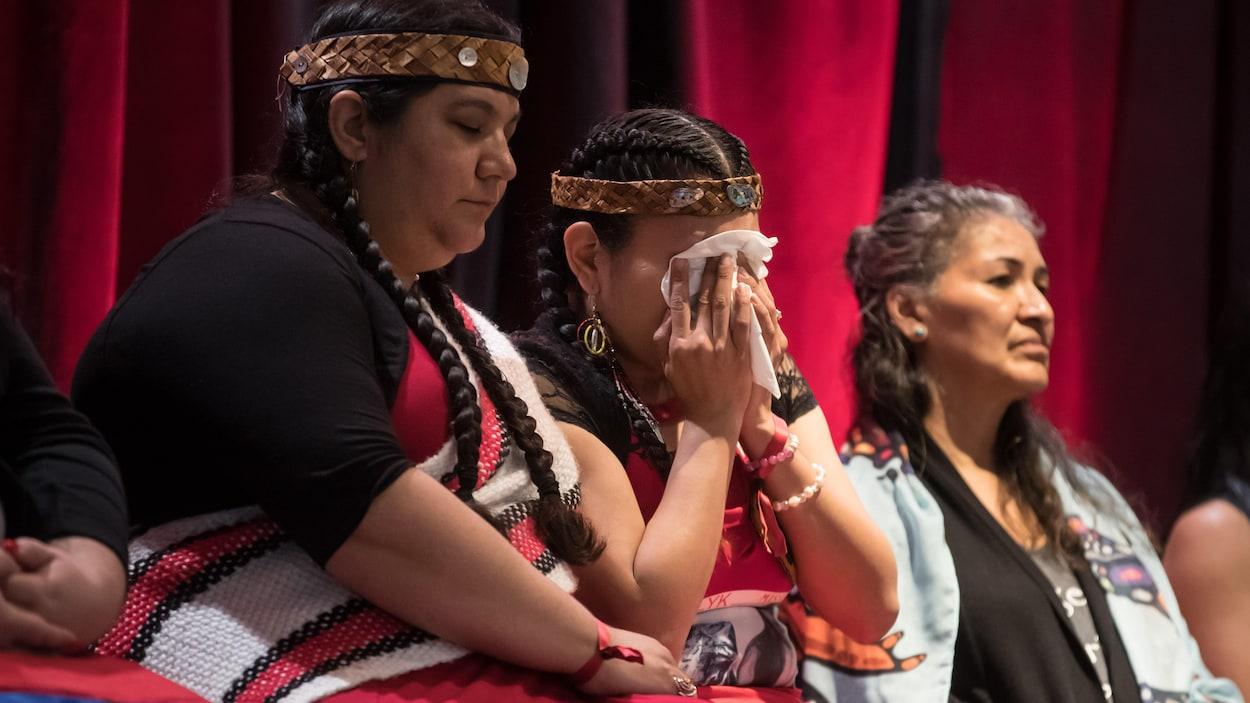 Trois femmes assistent à la présentation du rapport.
