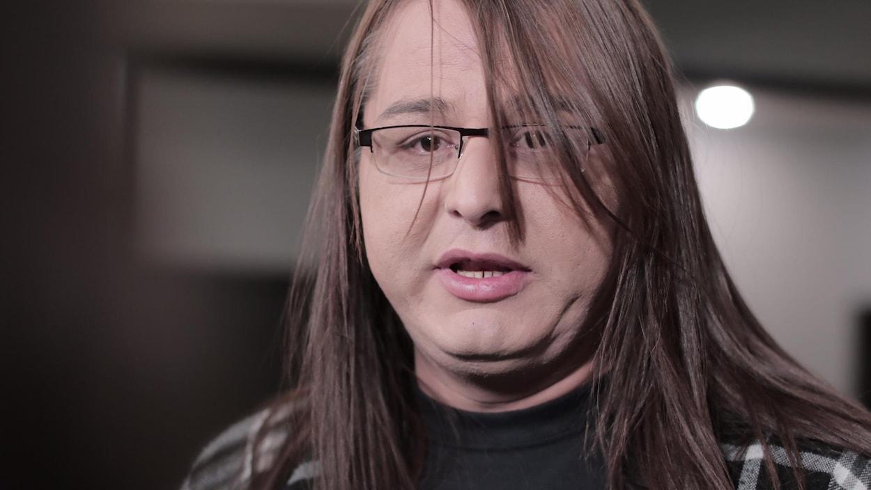 Gros plan sur le visage d'Alaya Mclvor, qui a les cheveux longs et porte des lunettes