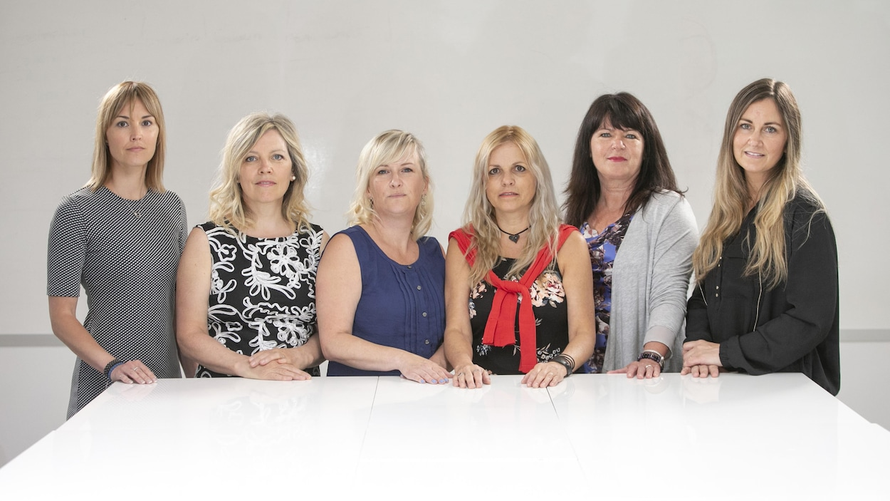 Debout, six femmes regardent la caméra.