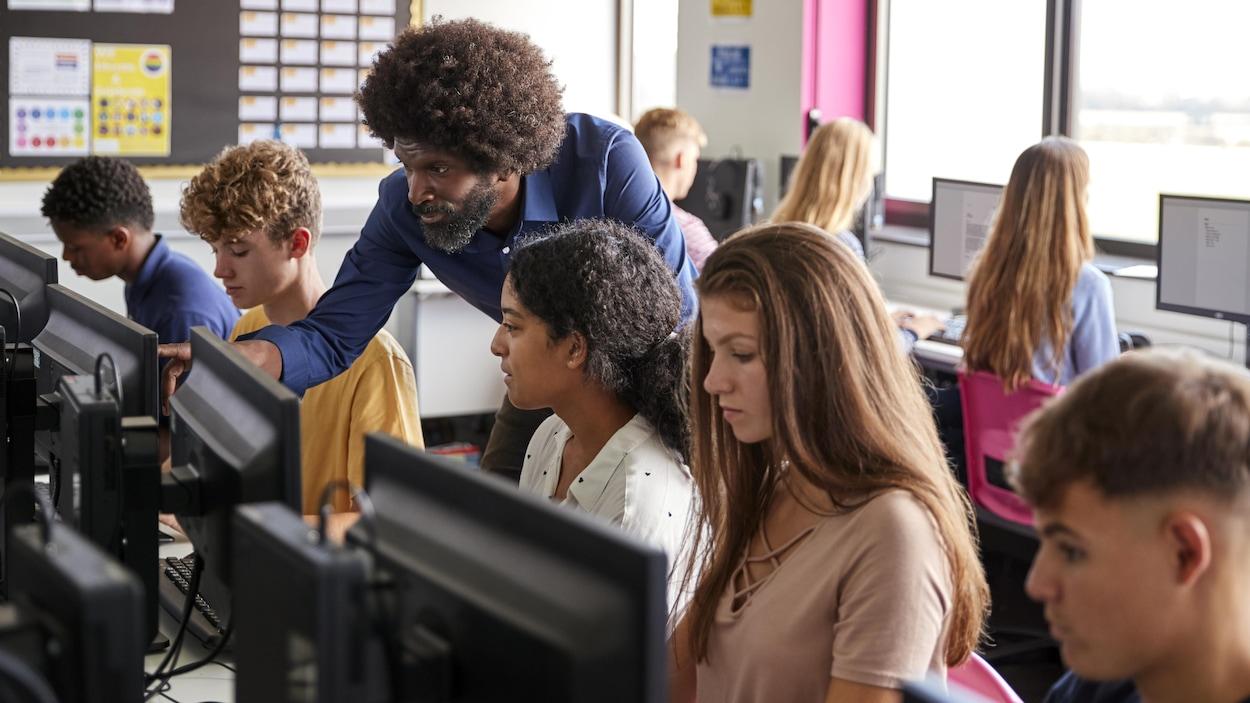 Un enseignant donne un cours à des élèves du secondaire dans une classe d'informatique.