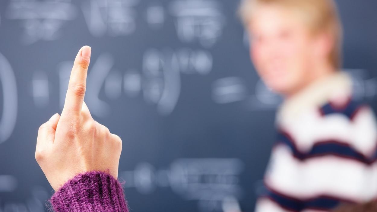 Le doigt levé d'une étudiante en classe.