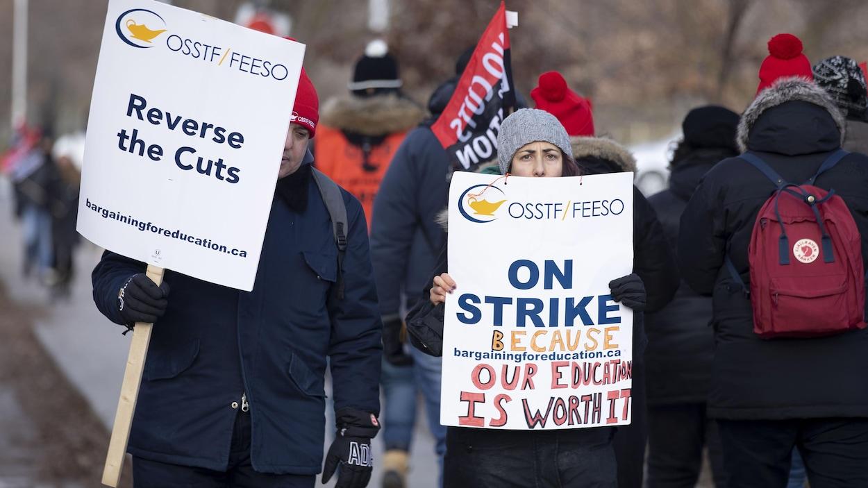 Des grévistes marchent et brandissent des pancartes qui dénoncent les compressions en éducation.