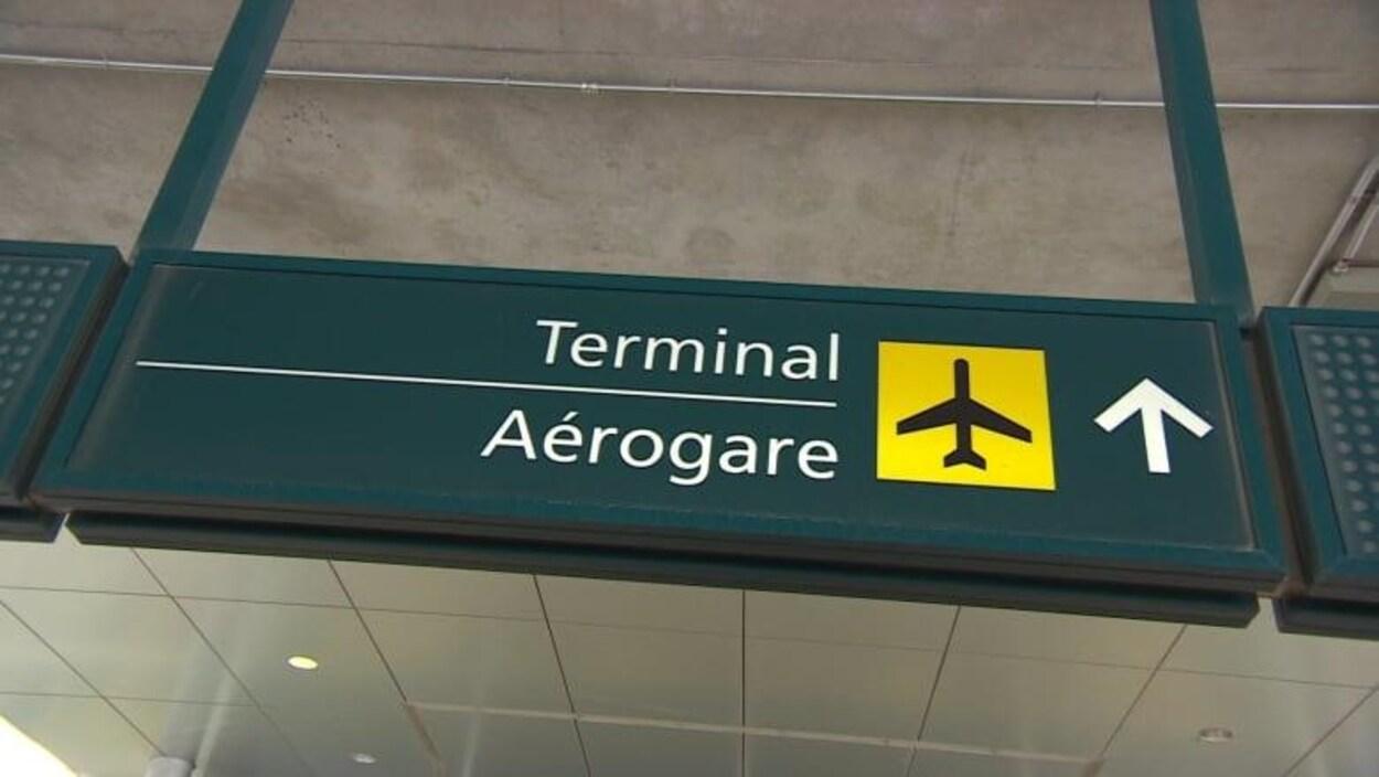Un enseigne indiquant la direction de l'aérogare dans un aéroport.