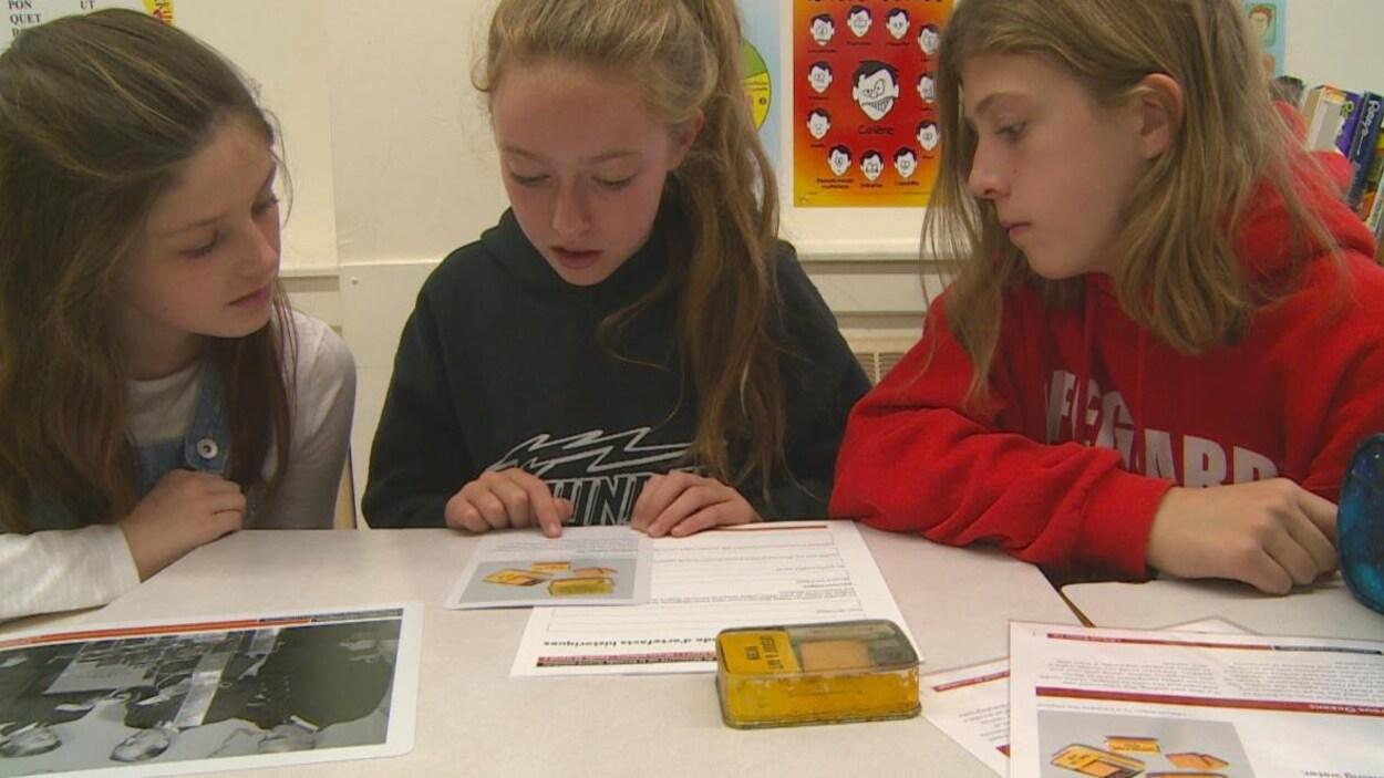 Trois jeunes élèves lisent un document dans une salle de classe.