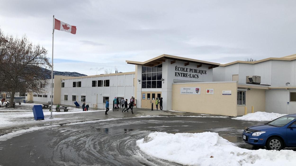 Plan large de la façade de l'école publique Entre-Lacs, on peut voir des élèves qui marchent vers la porte d'entrée de l'école.