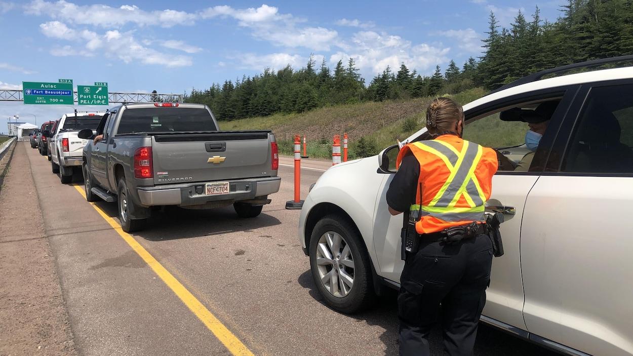 Une femme debout sur l'autoroute, de dos, portant une veste orange et jaune, parle à un automobiliste dans son véhicule.