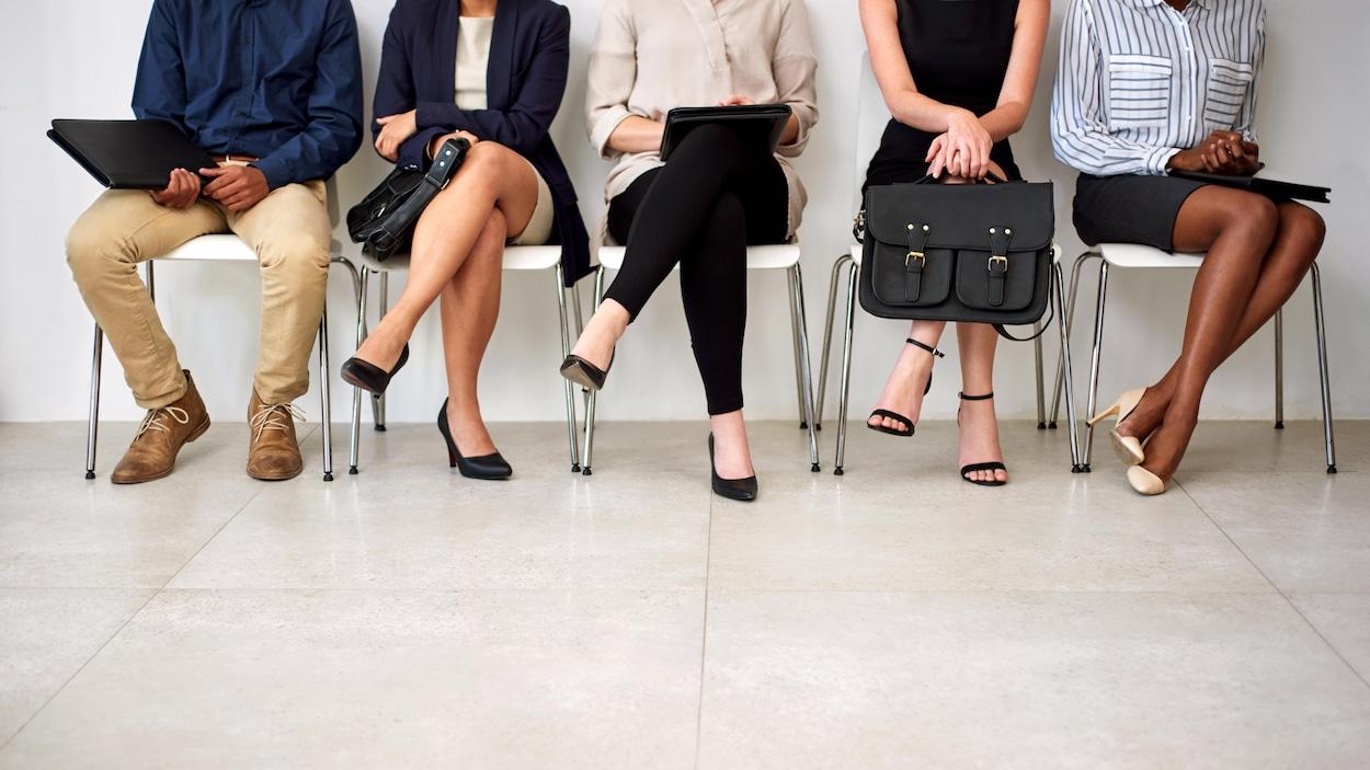 Des personnes assises sur des chaises de plastiques sont vues de face. On ne voit toutefois pas la figure des personnes. Certaines portent une jupe ou une robe, d'autres portent des pantalons.
