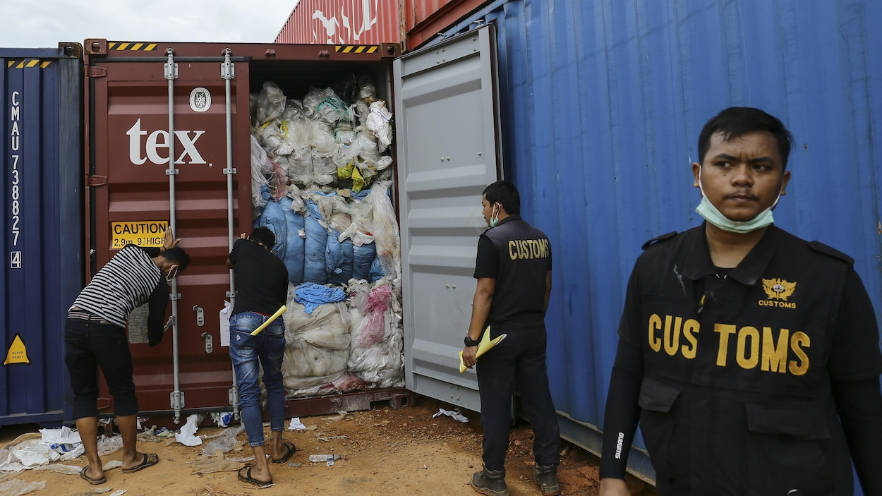 Des douaniers inspectent des conteneurs remplis de déchets plastiques.