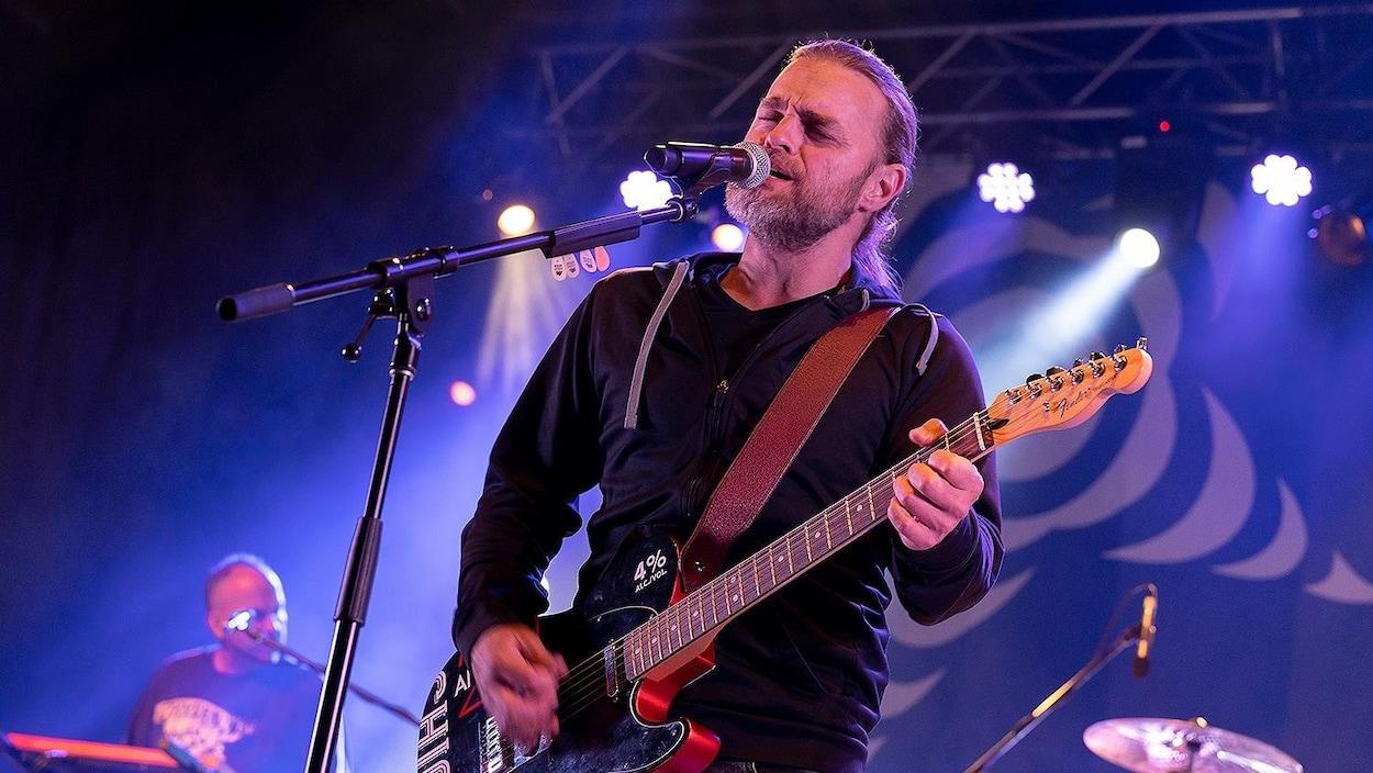 Le chanteur devant le micro, sur scène, qui joue de la guitare.