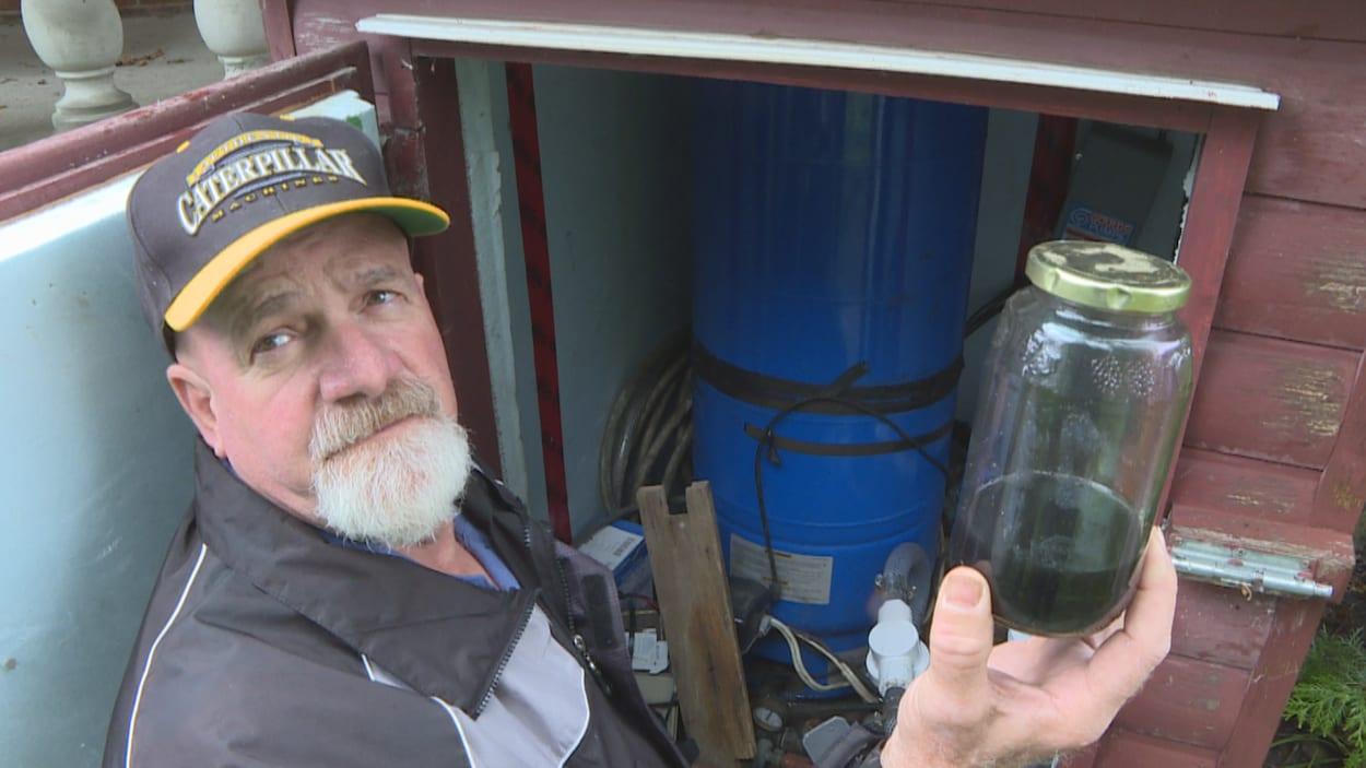 Marc tient dans sa main un bocal en verre avec de l'eau de couleur noire.